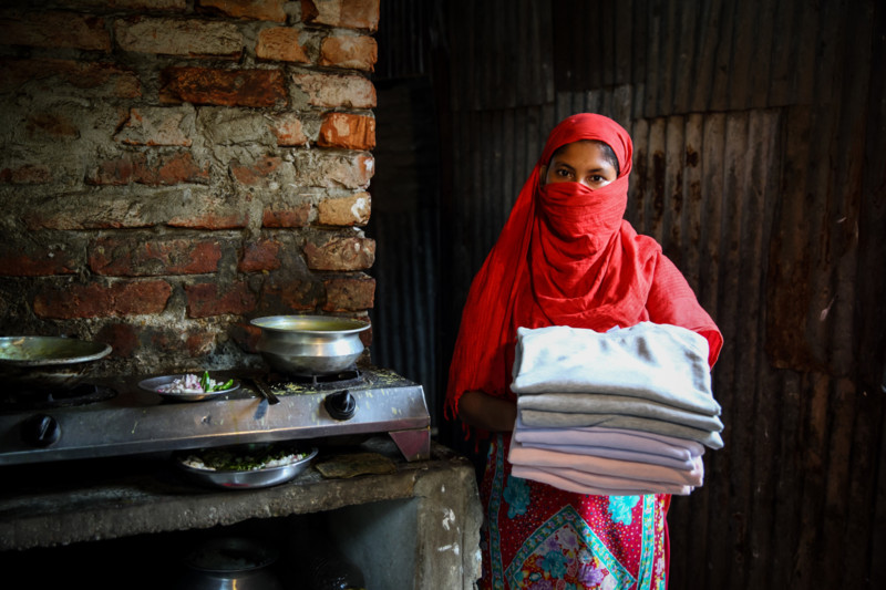 Garment worker, Forida (22) holds sweaters made in Bangladesh for an international brand. Oxfam 'What she makes' report.
