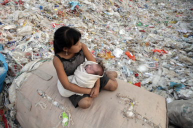 Plastic China documentary – girl sitting on a pile of recycling